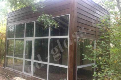Деревянная беседка со стеной из стекла